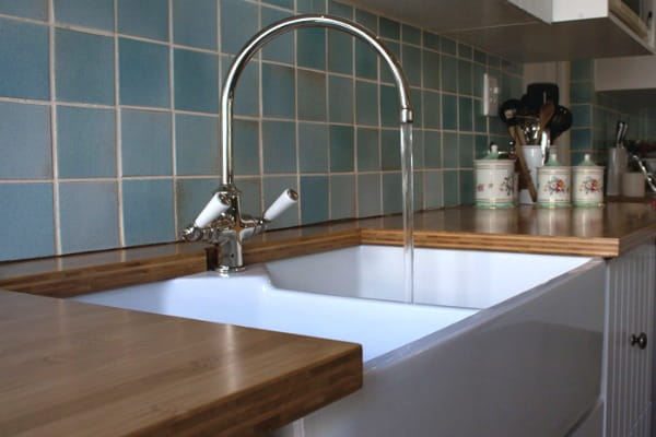 bamboo countertops with white farmhouse sink, blue tile backsplash