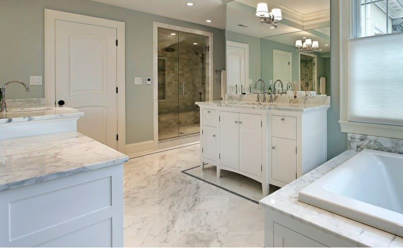 Carrara marble natural stone flooring and countertops in spa-like white bathroom