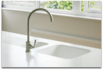 Corian sink molded into white countertops with drain board