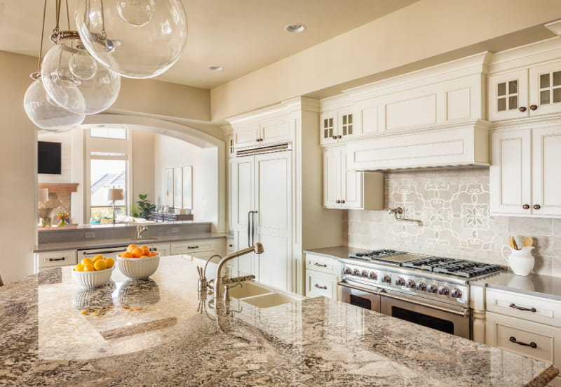 modern kitchen design with gray granite countertops on island and white cabinets