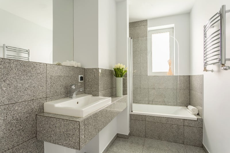 gray granite tile bathroom countertop, floor tiles, and tub surround with white sink and tub
