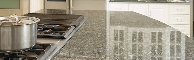A polished granite countertop is glossy, smooth, and reflective like a mirror