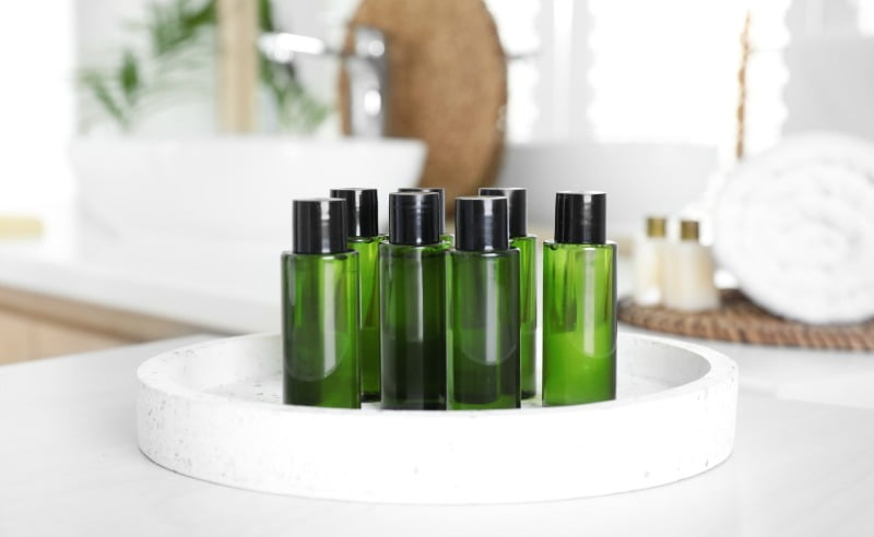 toiletry bottles on tray on marble bathroom countertop