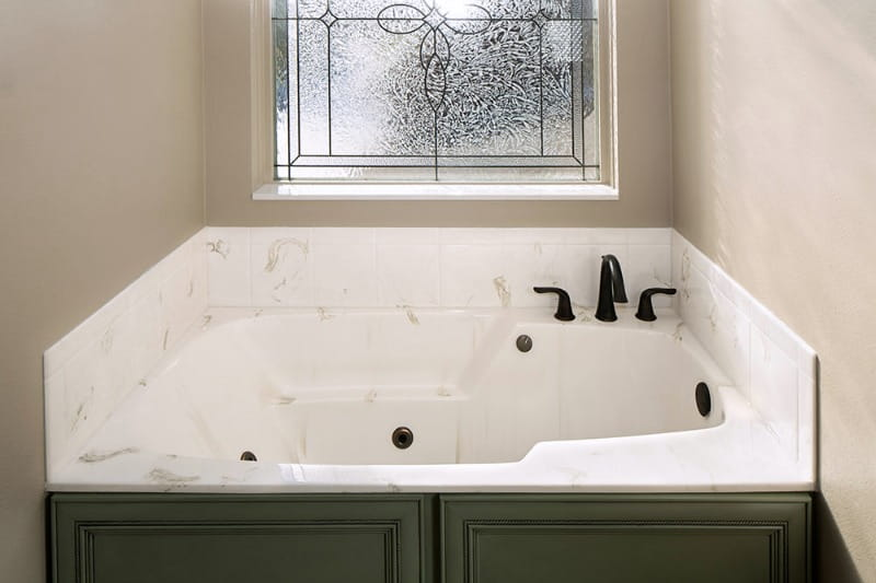 white cultured marble bathtub with jets under frosted window