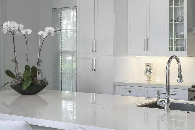 pure white polished neolith countertops in an upscale all white kitchen