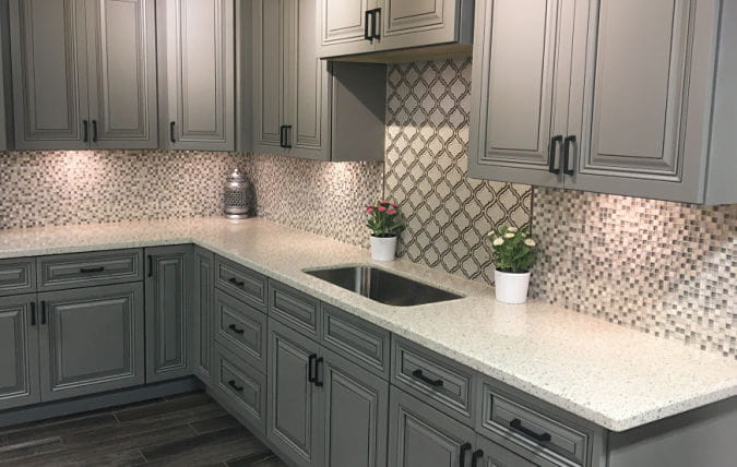 white quartz countertops on gray cabinets with glass tile backsplash